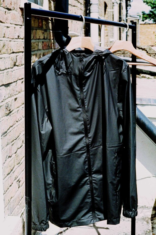 The RAINS Ultralight Jacket hanging on a rail outdoors. The Ultralight is our runner up pick for best rain jacket.